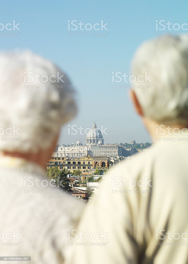 Couple standing, focus on st Peter's basilica in background royalty-free stock photo