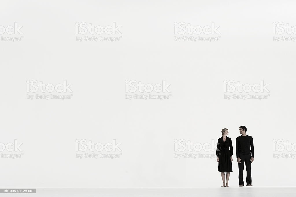 Couple standing in distance against white background, side view royalty-free stock photo