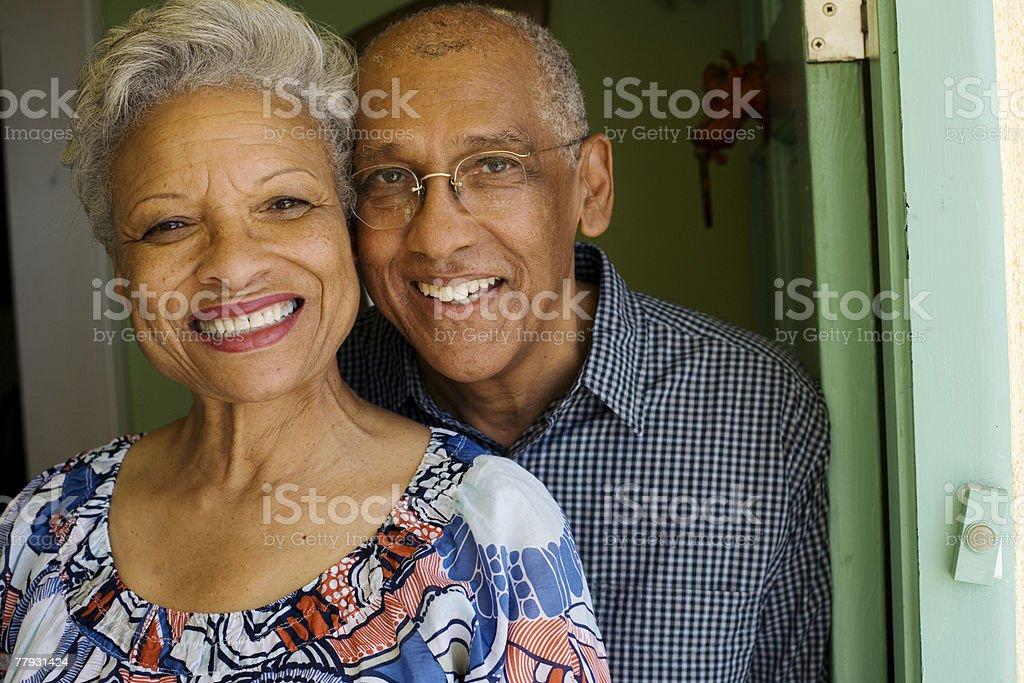 Couple standing in doorway smiling stock photo