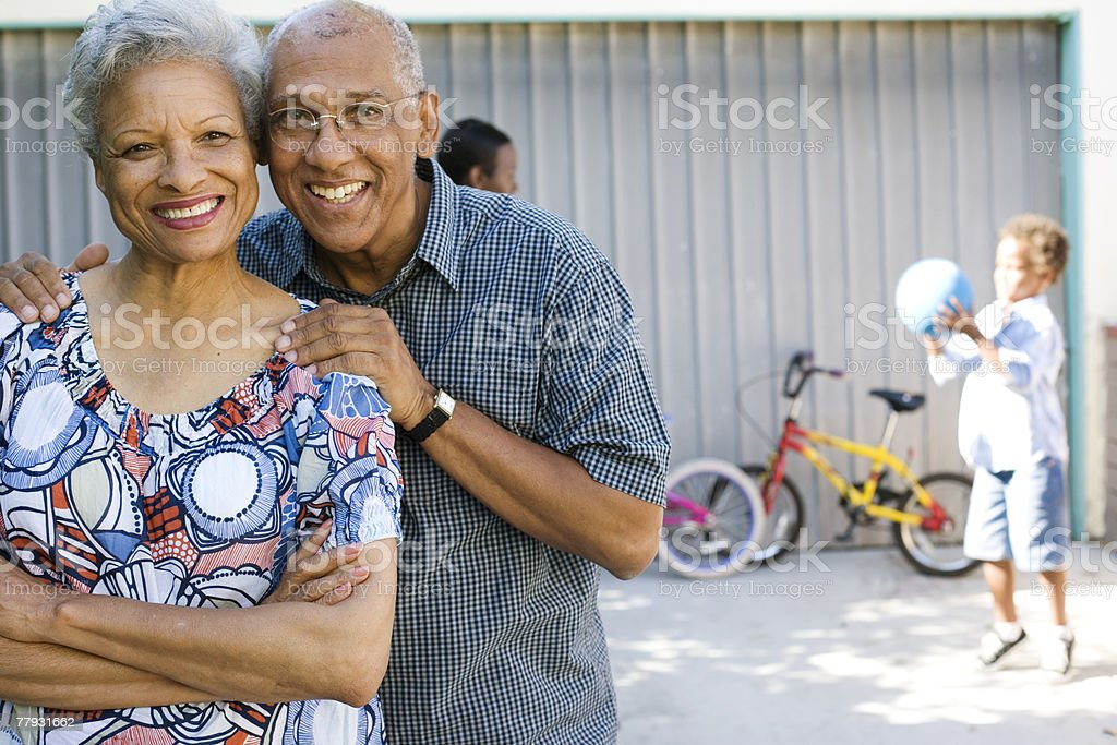 Couple standing in driveway with people in background stock photo