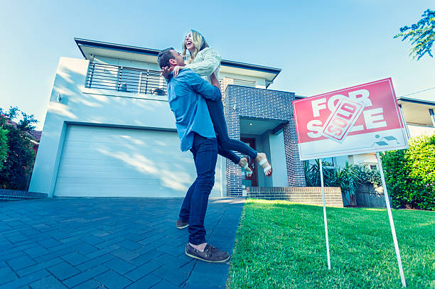 couple standing in front of a new home. - selling stock pictures, royalty-free photos & images
