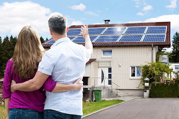 Couple Standing In Front Of Their House stock photo