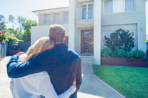 Paar steht vor ihrem neuen Zuhause. – Foto