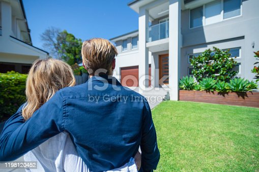 Couple standing in front of their new home. They are both wearing casual clothes and embracing. Rear view from behind them. The house is contemporary brick render, driveway, balcony and a green lawn. The front door is also visible. Copy space