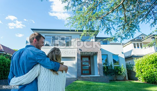 istock Couple standing in front of their new home. 504223726