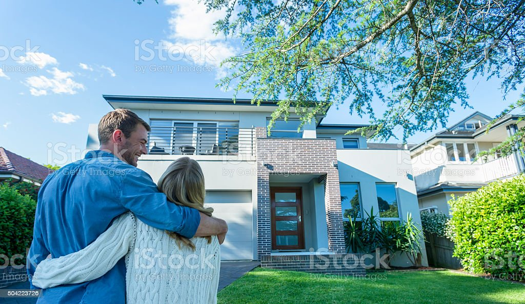 Couple standing in front of their new home. stock photo