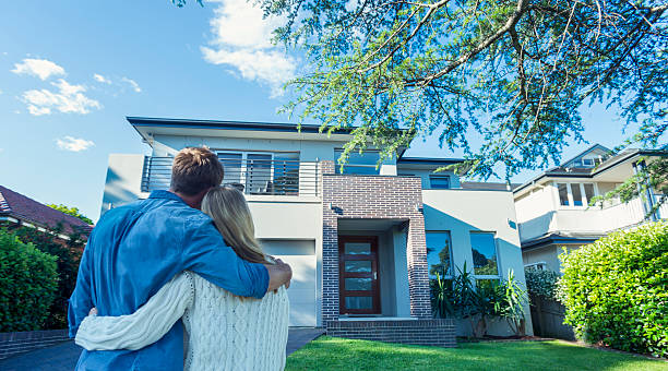 couple standing in front of their new home. - house hunting stock photos and pictures