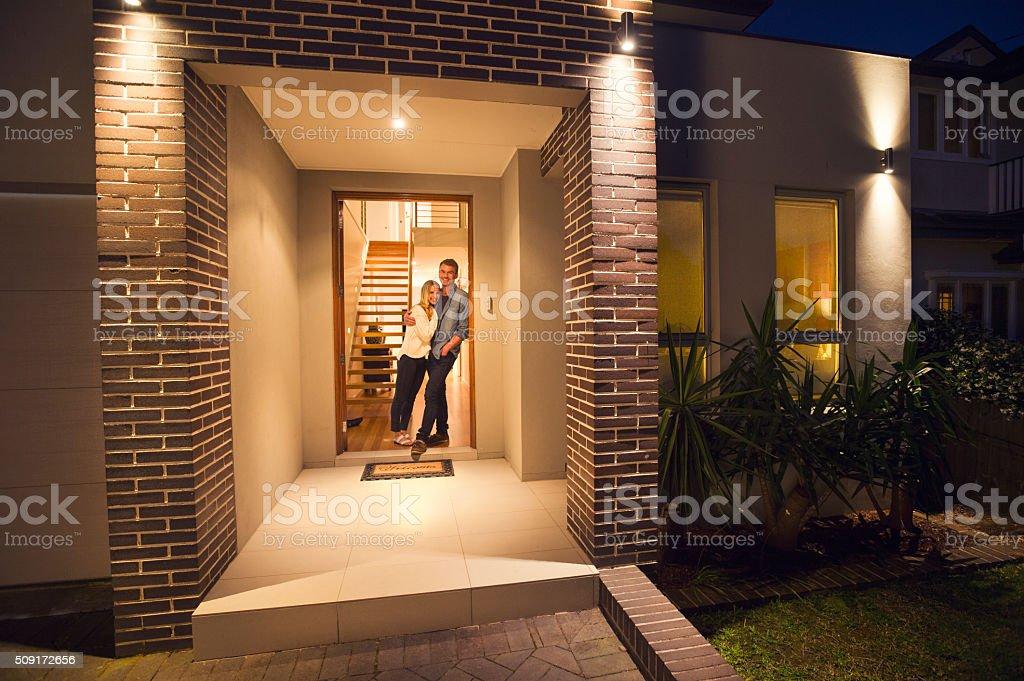 Casal em pé na frente de sua nova casa. - foto de acervo