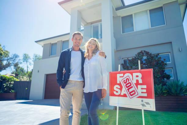 Ehepaar steht vor ihrem neuen Zuhause mit einem verkaufsoffenen Schild. – Foto