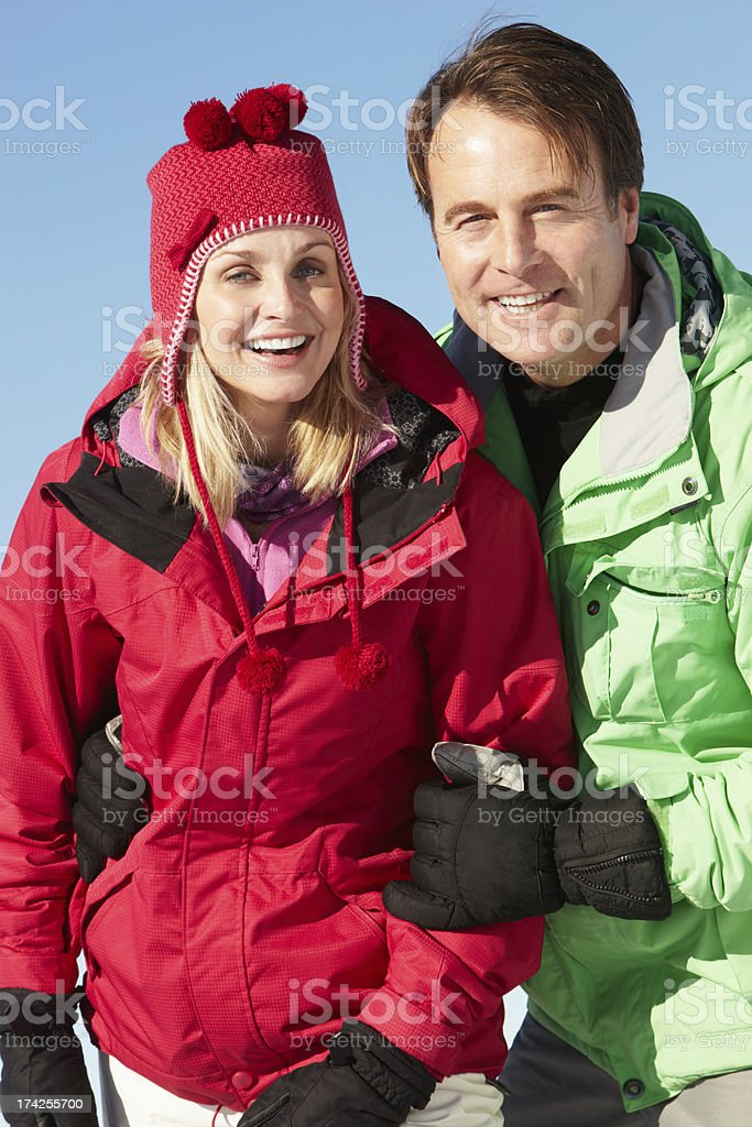 Couple Standing In Snow Wearing Warm Clothes On Ski Holiday stock photo