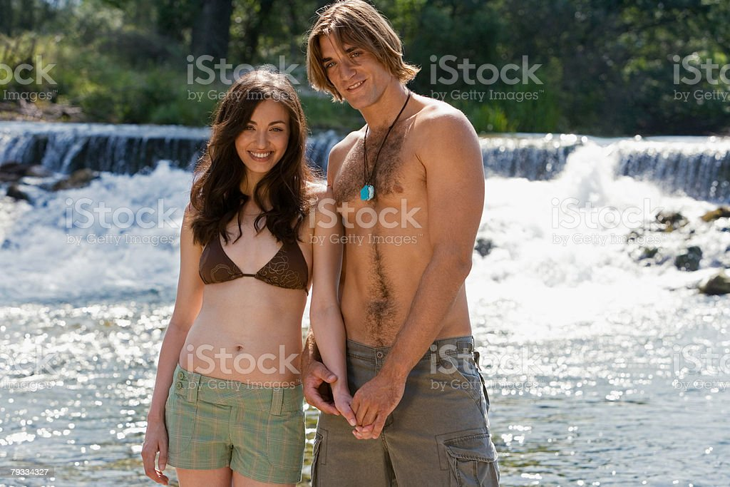 Couple standing near a waterfall royalty-free stock photo