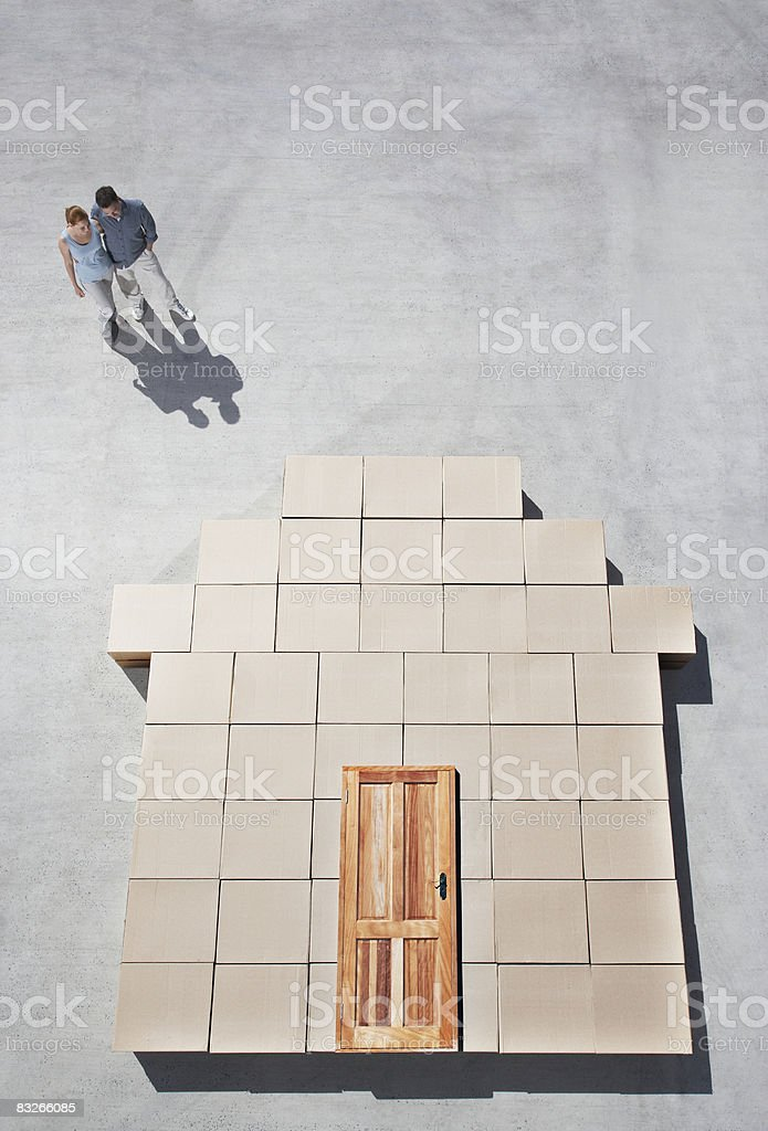 Couple standing next to house outline on sidewalk royalty-free stock photo