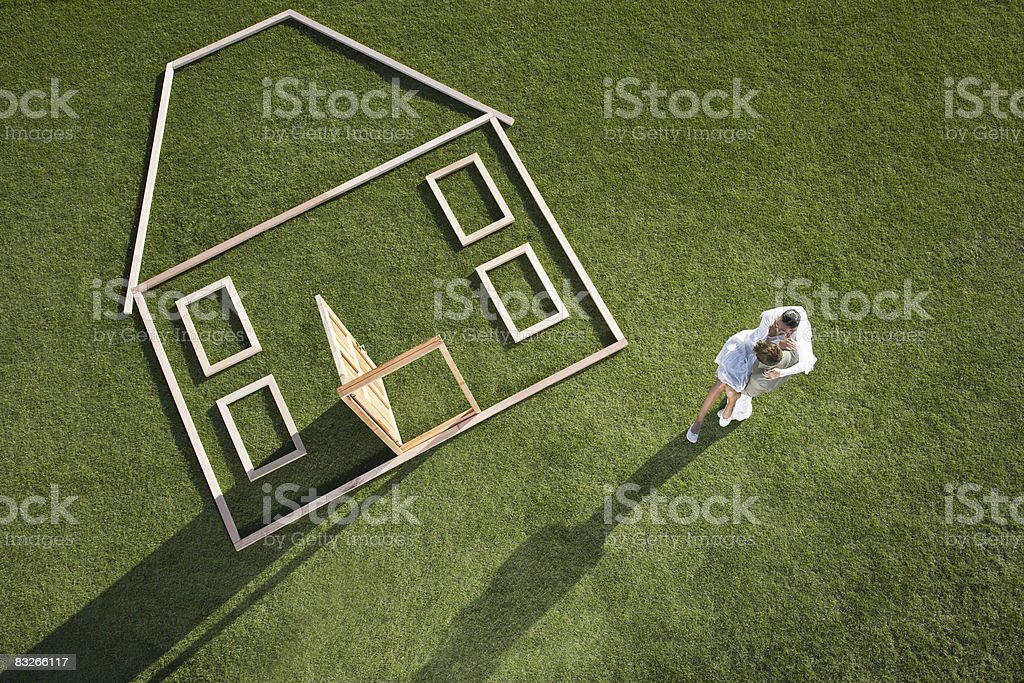 Couple standing next to house outline stock photo