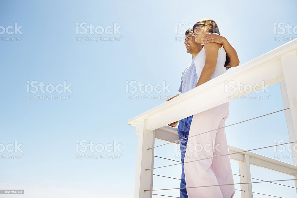 Couple standing on balcony looking at sky royalty-free stock photo