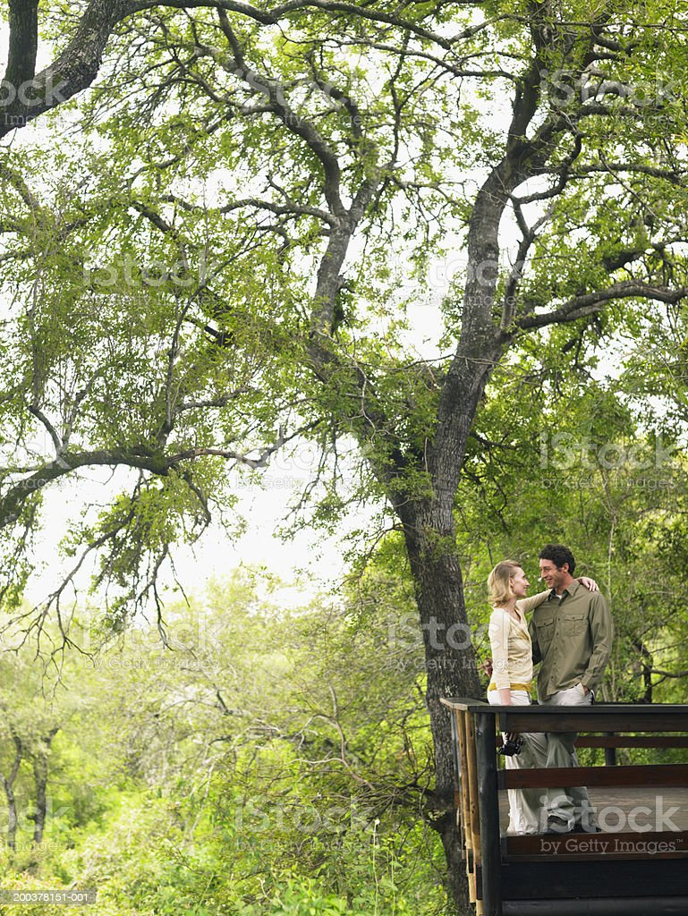 Couple standing on balcony of lodge, smiling at each other royalty-free stock photo
