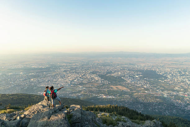 Couple standing on mountain peak and pointing at the city stock photo