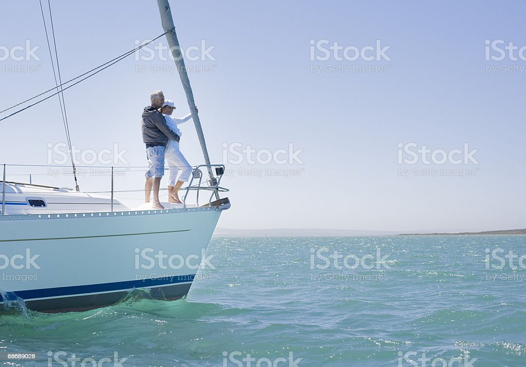 Couple standing on sailboat stock photo