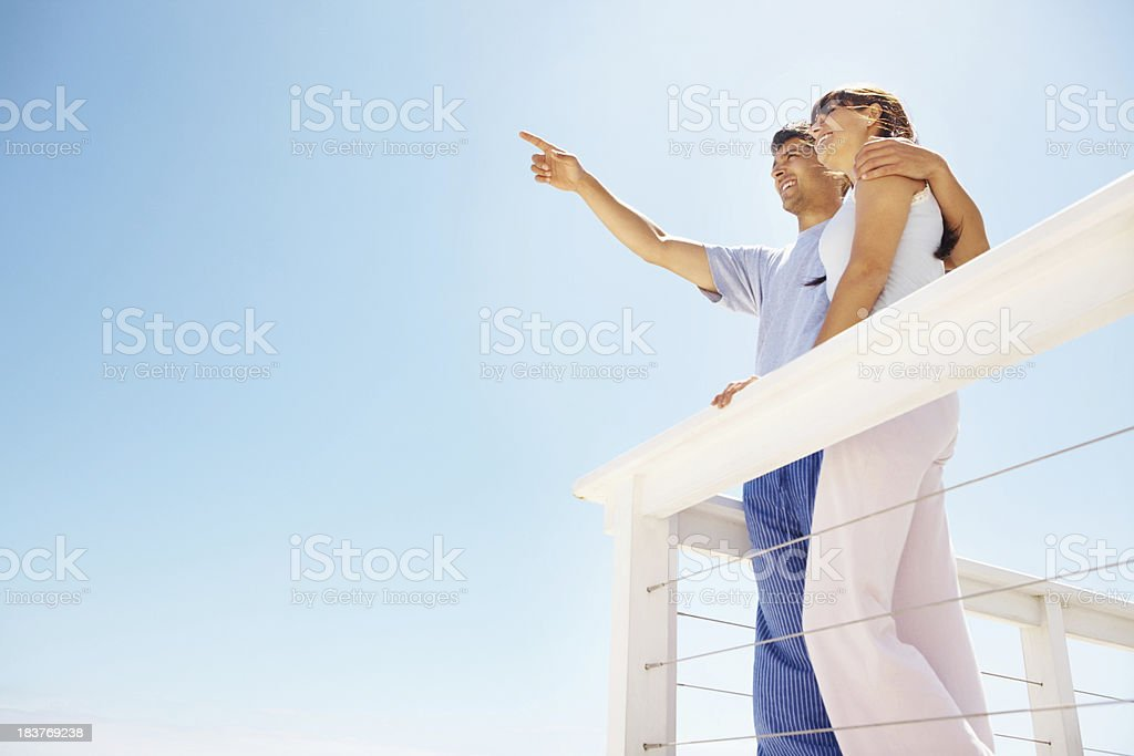 Couple standing on the balcony Low angle view of couple standing on the balcony with man pointing at copyspace 20-29 Years Stock Photo