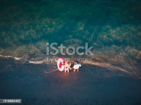 Couple holding hands while standing by the seaside and enjoying the sunset top down aerial view with copy space. Summer vacation and travel season abstract