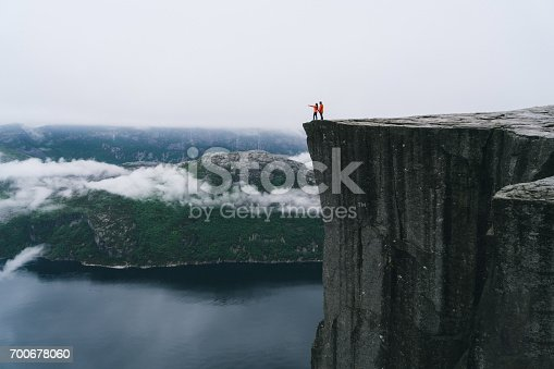 Young Caucasian couple standing  on the Preikestolen in Norway