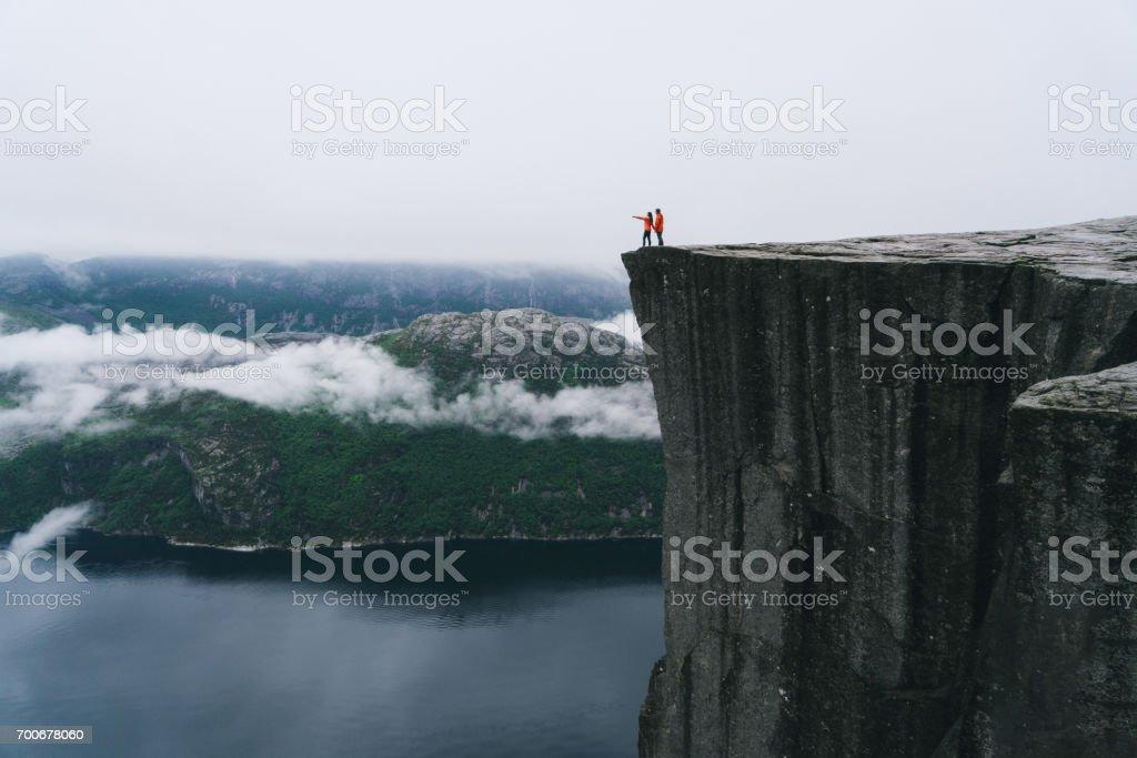 Pareja de pie en el Preikestolen en Noruega - foto de stock