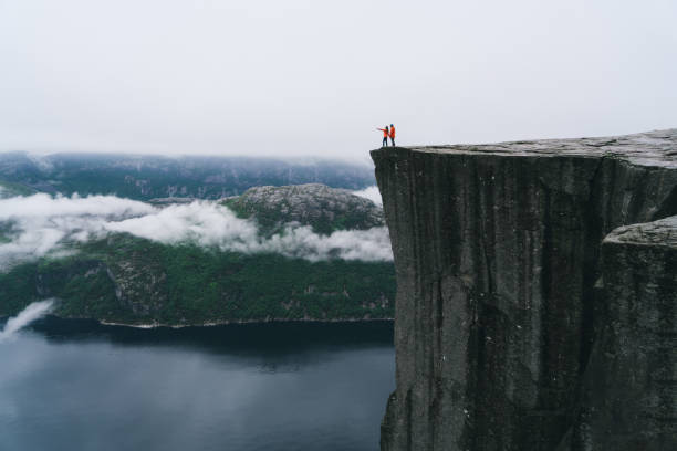 couple standing  on the preikestolen in norway - cliff stock pictures, royalty-free photos & images
