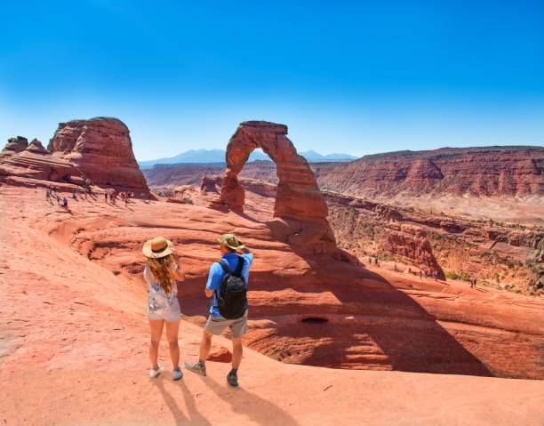 Couple standing on top of the mountain looking at beautiful view. Couple on vacation hiking trip. Man and woman standing on top of the mountain looking at beautiful view. Delicate Arch,  Moab, Utah, Arches National Park. delicate arch stock pictures, royalty-free photos & images