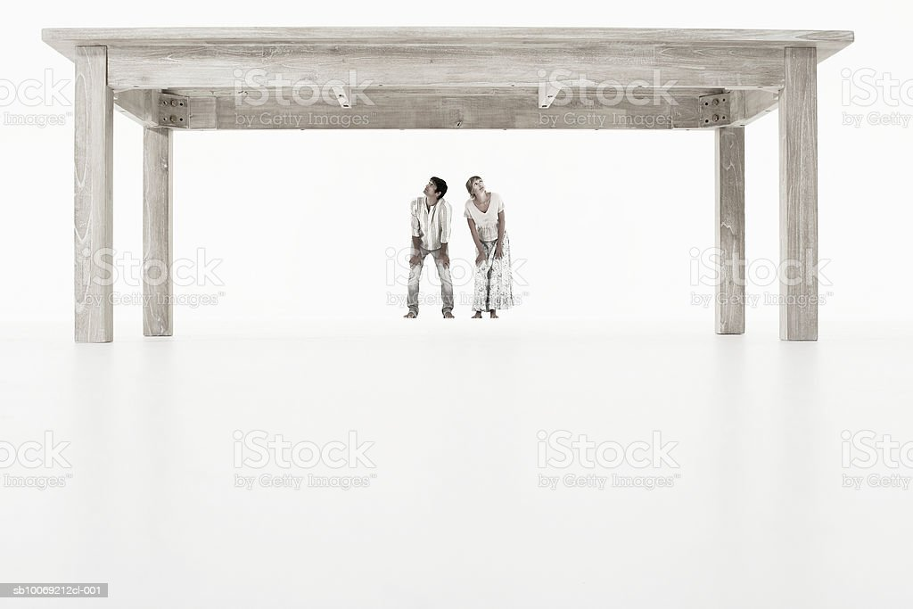 Couple standing under oversized wooden table against white background royalty-free stock photo