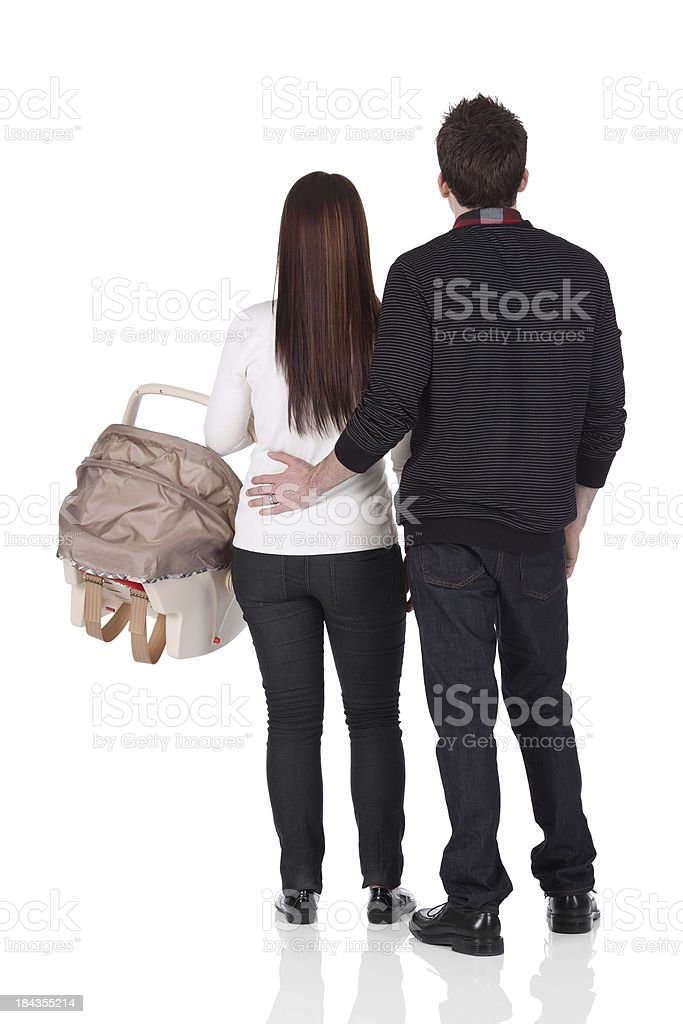 Couple standing with a baby seat royalty-free stock photo