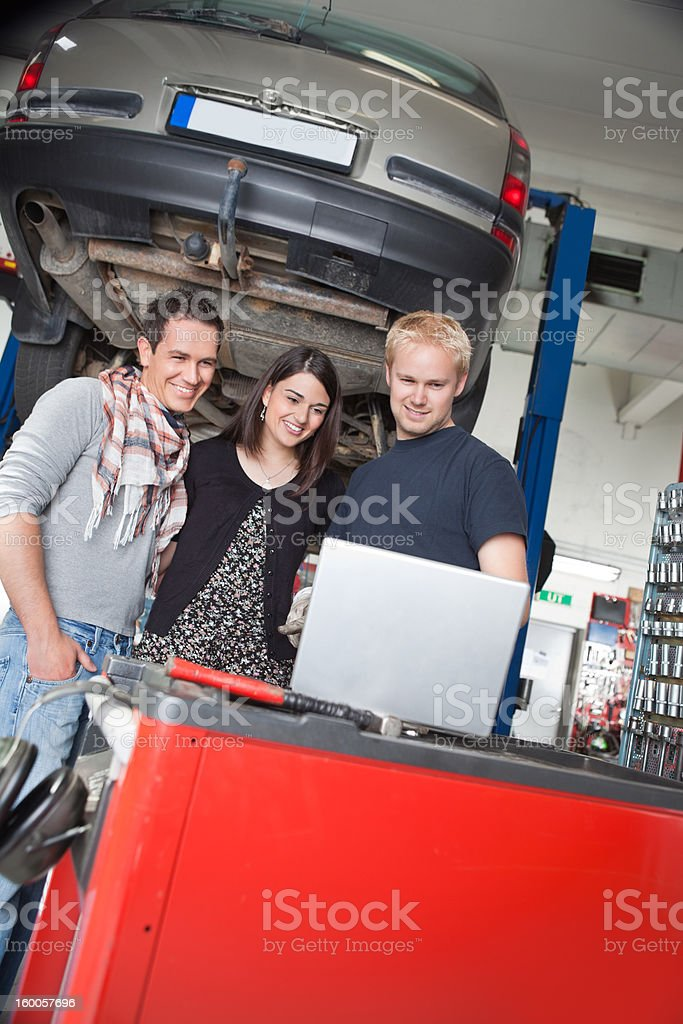 Couple standing with mechanic using laptop royalty-free stock photo