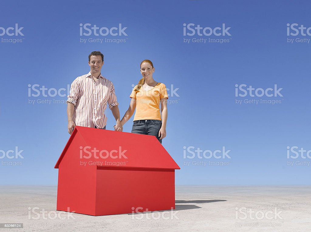 Couple standing with small model house in desert royalty free stockfoto