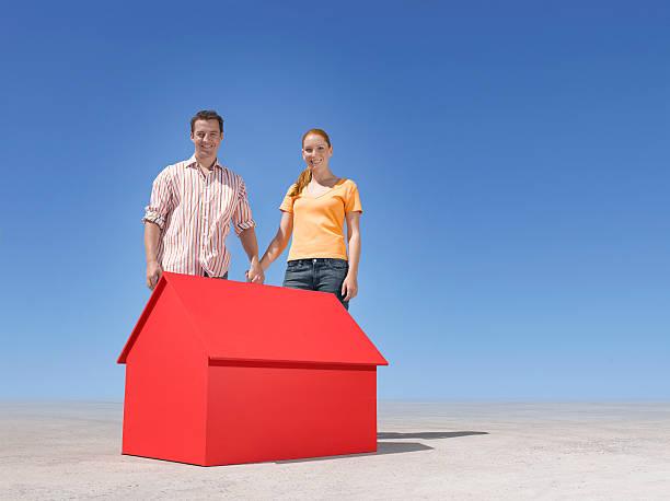 Paar stehend mit kleinen Modell-Haus in der Wüste – Foto