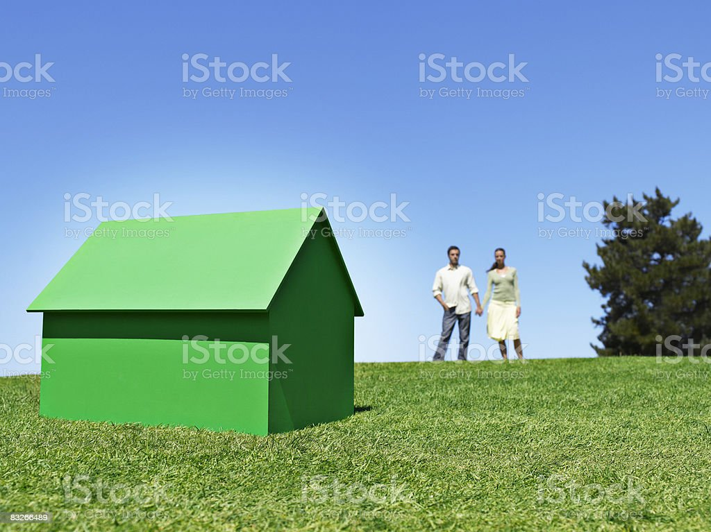 Couple standing with small model house royalty-free stock photo