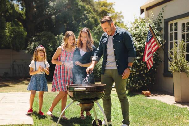 pareja de pie con sus hijos en su patio trasero haciendo barbacoa - grilling fotografías e imágenes de stock