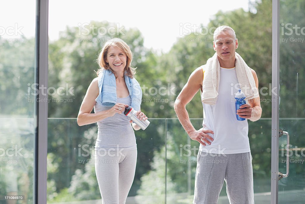 Couple standing with towels and water bottles stock photo