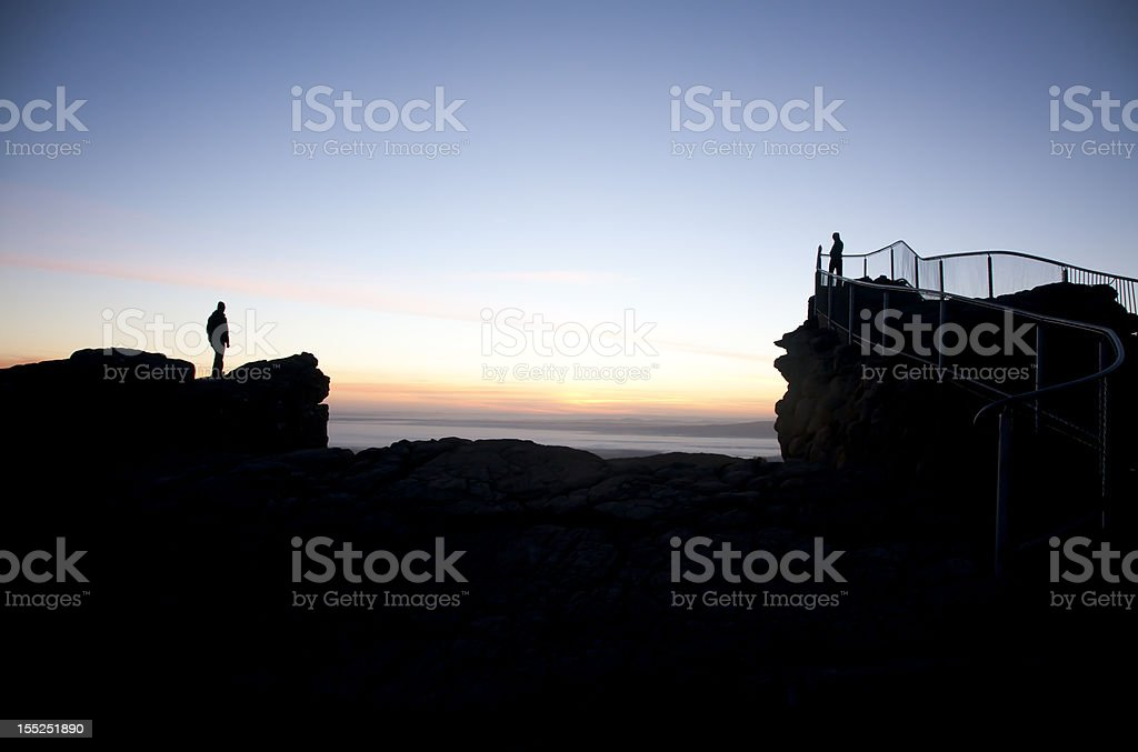 Couple stands apart at lookout stock photo