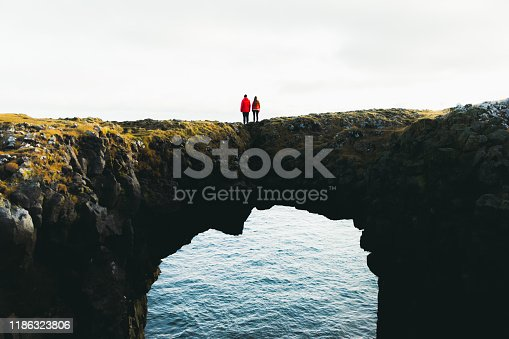 Young woman and man in red jackets enjoying their journey at Snaefellsnes Peninsula in West Iceland, walking at huge natural arch above the sea