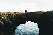 istock Couple stay on the beautiful arch looking at the sea in Iceland 1186323806