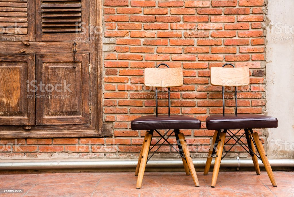 Couple steel frame chairs are padded with brown cushions and a wooden backrest stock photo