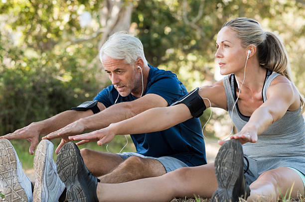 Couple stretching at park Mature couple stretching at park and listening to music. Athletic senior couple exercising together outdoor. Fit senior runners stretching before running outdoors. touching toes stock pictures, royalty-free photos & images