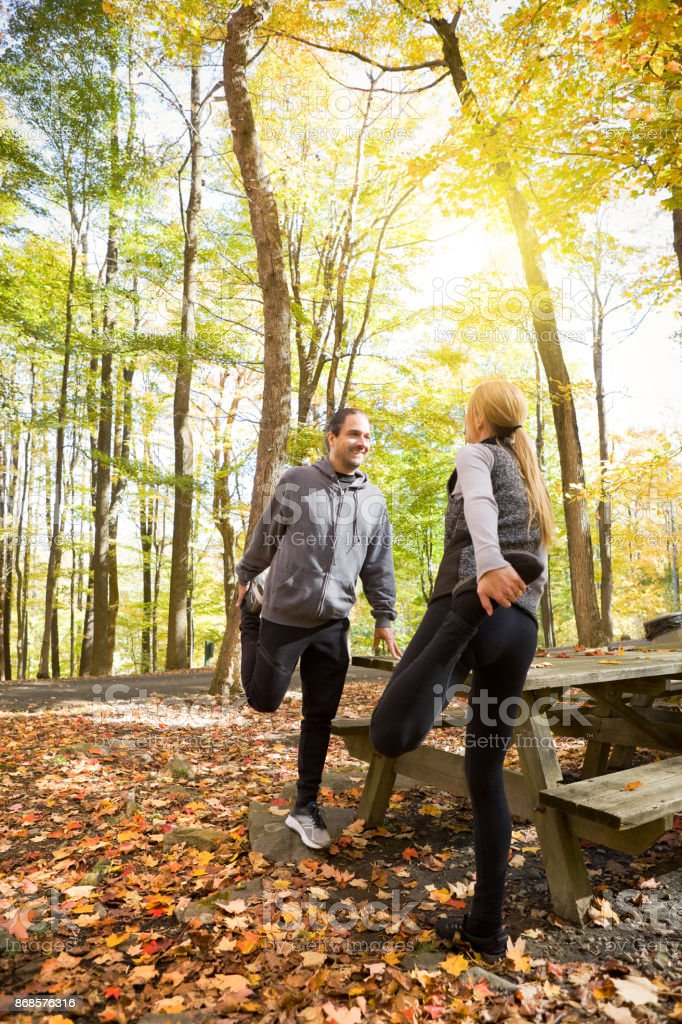Couple Stretching Before Autumn Run A couple in their 40's chatting as the stretch for a run on a beautiful fall day. 45-49 Years Stock Photo