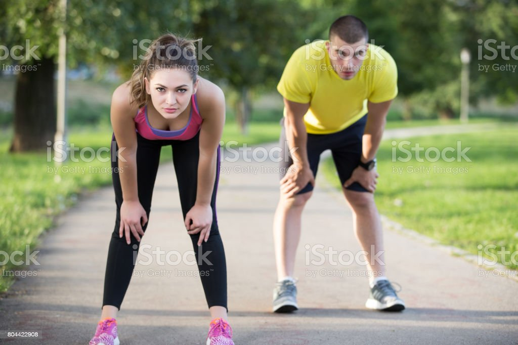 Couple stretching before jogging at the bench in the park stock photo