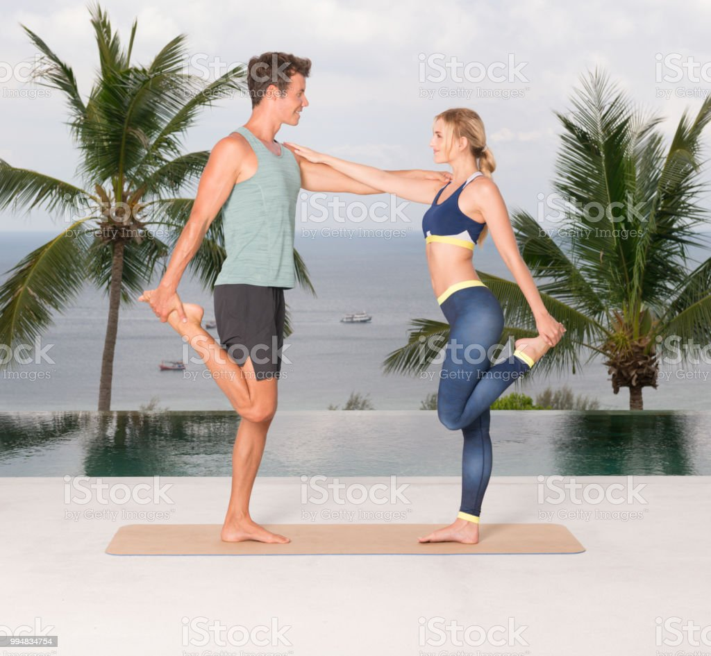 Couple Stretching, Personal Trainer, Fitness Coach on Vacation by the...