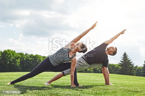 Couple stretching. Young couple stretching and doing yoga exercises in nature on a sunny morning. Healthy lifestyle concept. Acro yoga