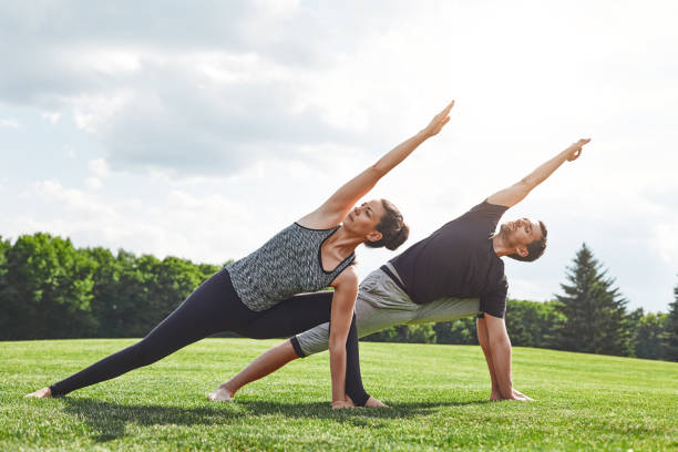 couple stretching. young couple stretching and doing yoga exercises in nature on a sunny morning. healthy lifestyle concept - aktywny tryb życia zdjęcia i obrazy z banku zdjęć
