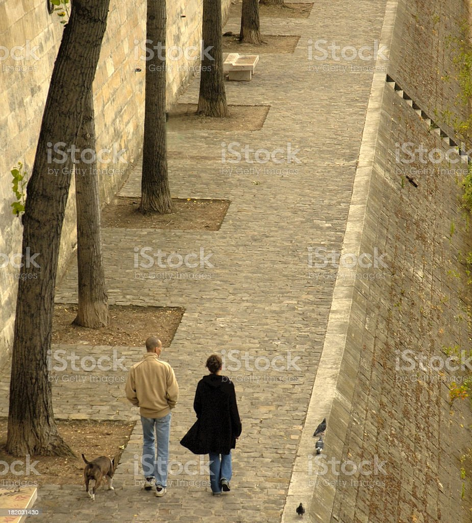 Couple strolling along the Seine River in Paris, France. royalty-free stock photo