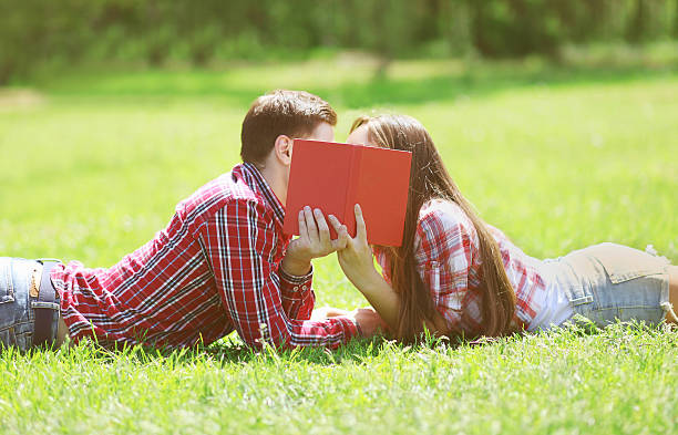 Couple students in love kissing on the grass stock photo