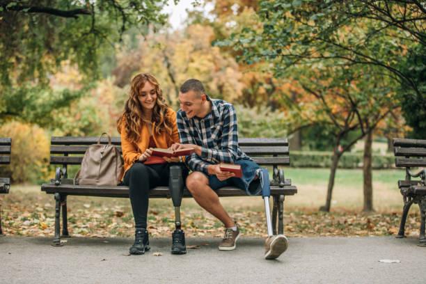 couple studying together in park - compagni scuola foto e immagini stock