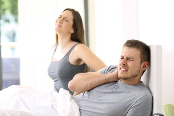 Couple suffering ache in a not comfortable bed stock photo