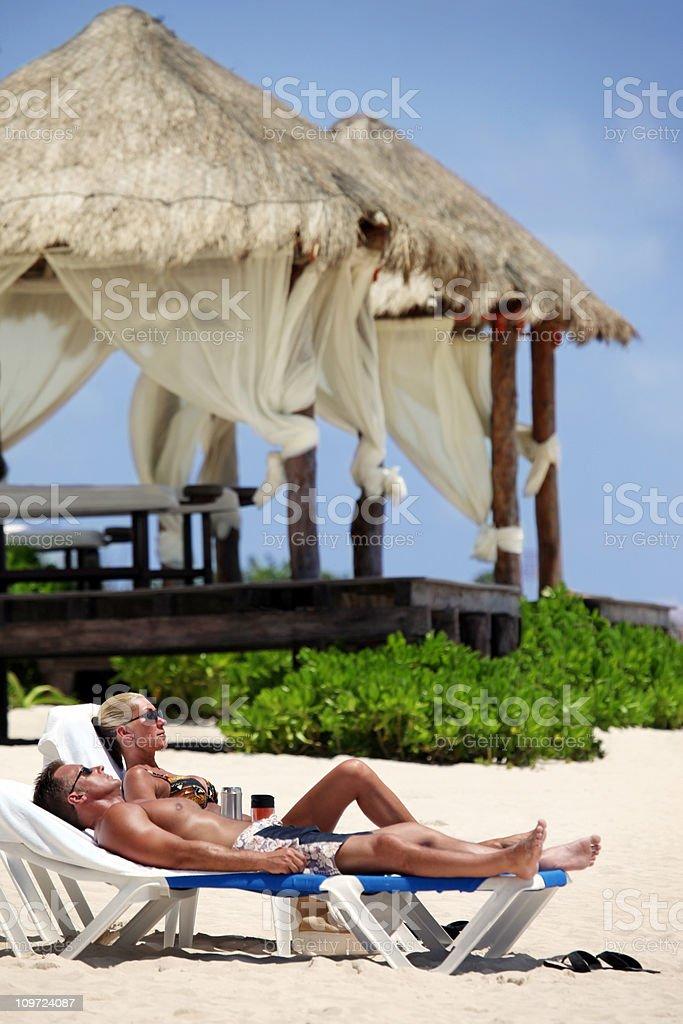 Couple Sunbathing at Resort royalty-free stock photo